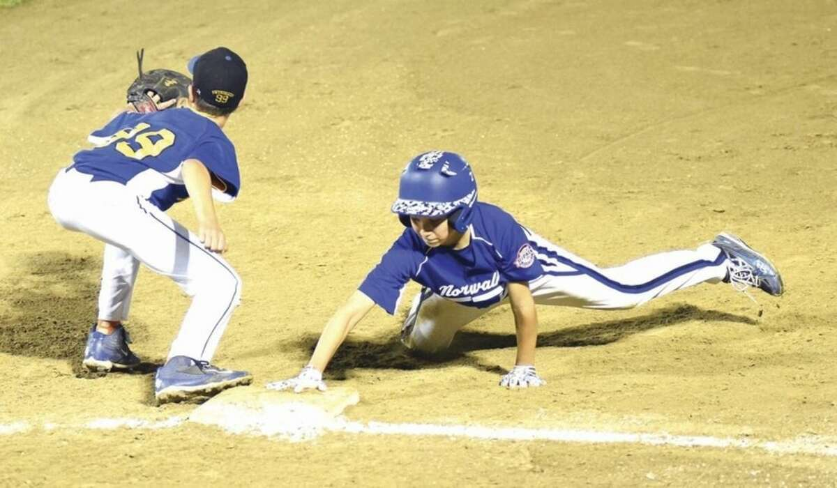 Hour photo/John Nash Norwalk's Ben Boccanfuso, right, dives back into first base on a pick-off play against Newtown on Tuesday in a winner's bracket final at the New England Regional Cal Ripken 11-year-old All-Star tournament at Beckwith Park in Dover, N.H. Newtown won the game 3-2.