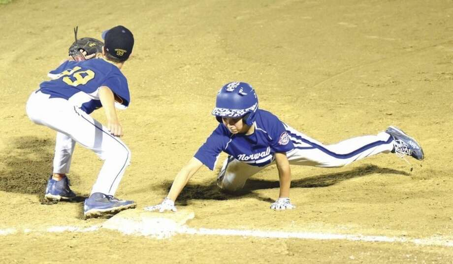 Hour photo/John NashNorwalk's Ben Boccanfuso, right, dives back into first base on a pick-off play against Newtown on Tuesday in a winner's bracket final at the New England Regional Cal Ripken 11-year-old All-Star tournament at Beckwith Park in Dover, N.H. Newtown won the game 3-2.