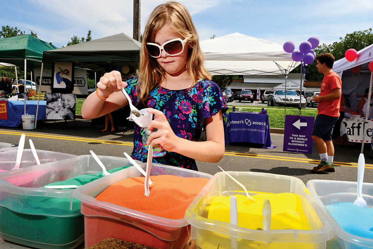 Hour photo / Erik Trautmann 8 year old Olivia Letsch dives into the Sandart Party during to the 3rd annual Wilton Street Fair and Sidewalk Sale in Wilton Center Saturday.