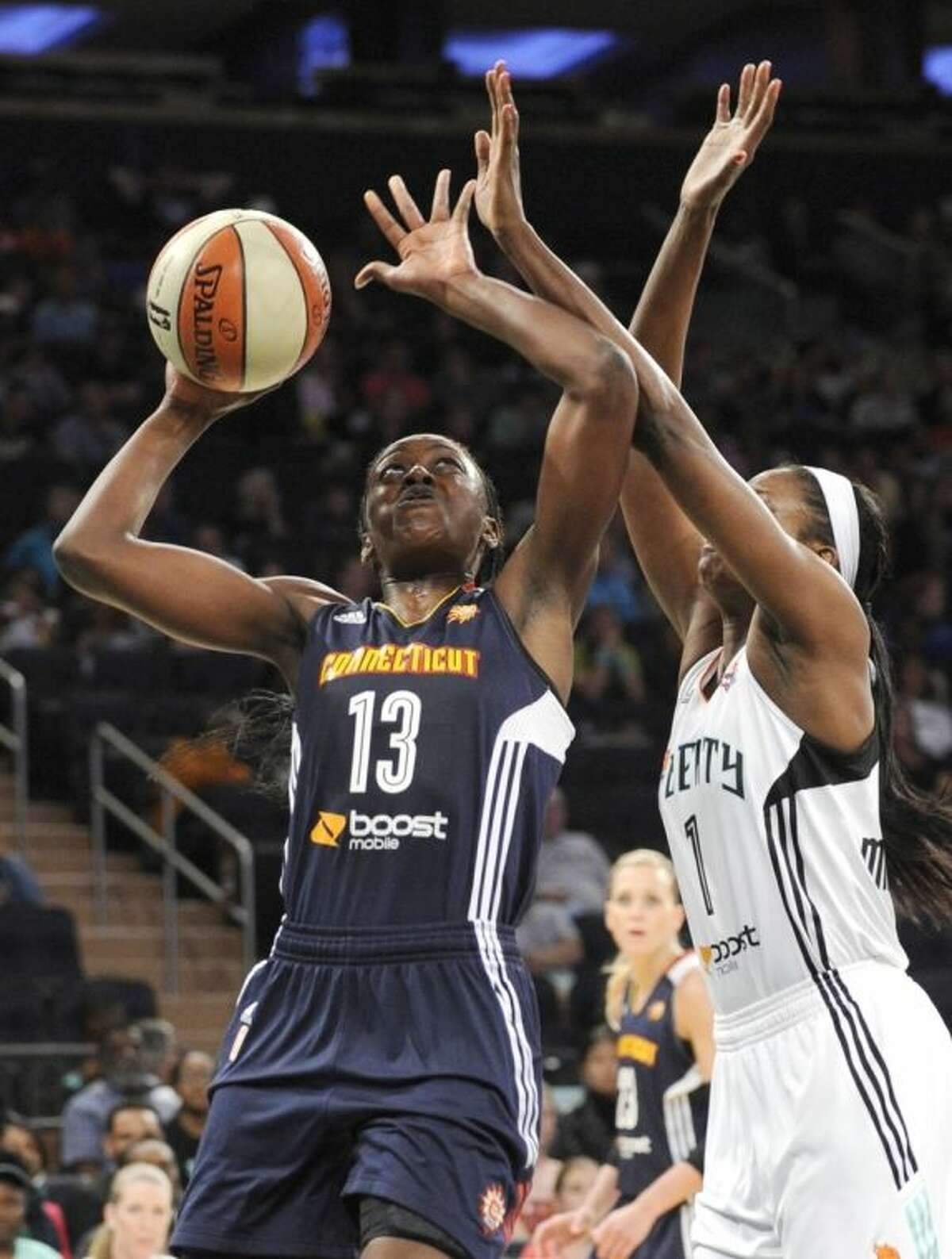 FILE - In this June 13, 2014, file photo, Connecticut Sun forward Chiney Ogwumike, left, shoots as New York Liberty forward Delisha Milton-Jones defends during the second quarter of a WNBA basketball game at Madison Square Garden in New York. Chiney will face her sister Nneka on Sunday, when the Sun host the Los Angeles Sparks. (AP Photo/Bill Kostroun, File)