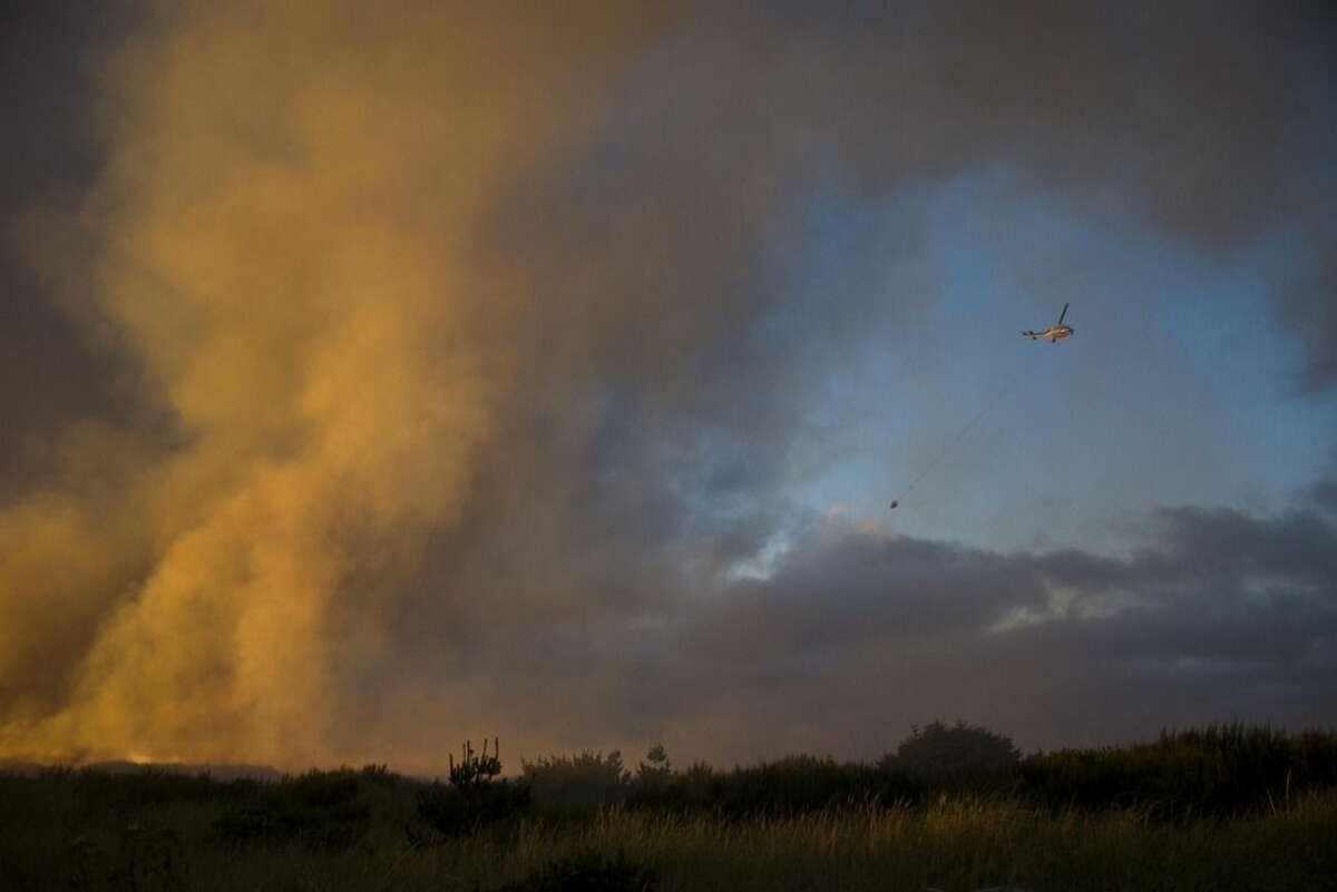 In this Aug. 3, 2015 photo, a helicopter flies overhead and dumps water as firefighters work to contain a brush fire near the South Jetty at Fort Stevens State Park in Warrenton, Ore. Numerous other wildfires in California, Washington state and Oregon took off as the effects of drought and summer heat turned the West Coast combustible. (Joshua Bessex/Daily Astorian via AP) MANDATORY CREDIT
