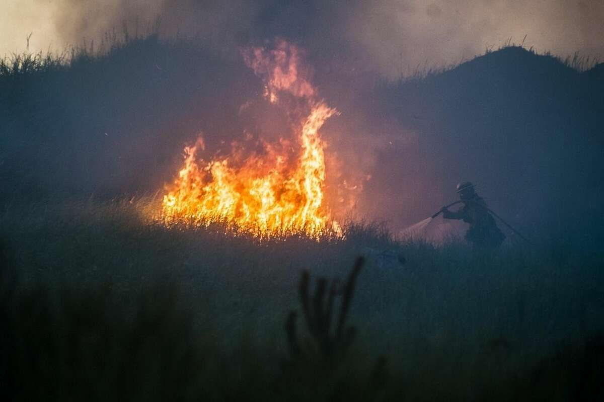 In this Aug. 3, 2015 photo, a firefighter hoses down part of a brush fire near the South Jetty at Fort Stevens State Park in Warrenton, Ore. Numerous other wildfires in California, Washington state and Oregon took off as the effects of drought and summer heat turned the West Coast combustible. (Joshua Bessex/Daily Astorian via AP) MANDATORY CREDIT