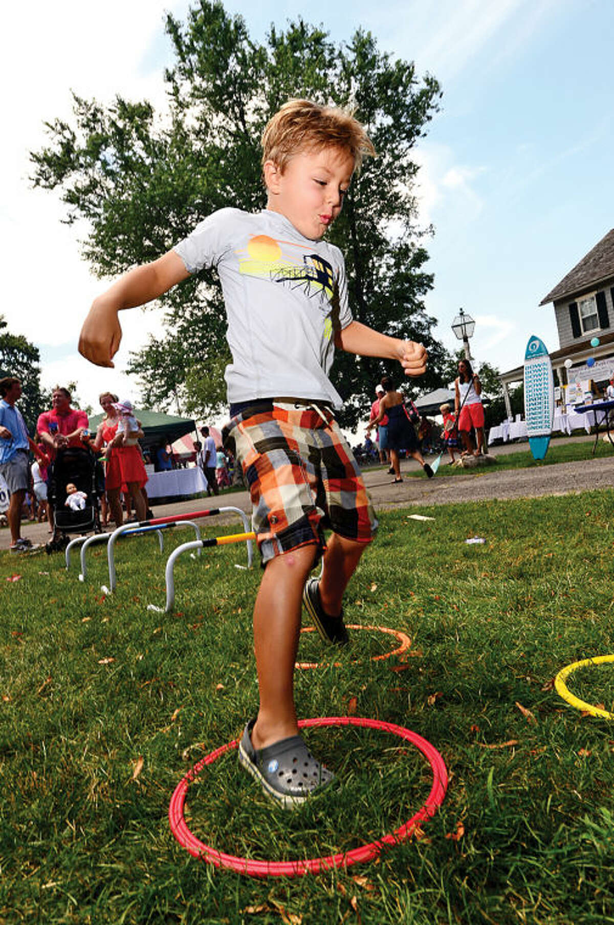 Hour photo / Erik Trautmann Reilly Tanner runs the obstacle course at the 44th Annual River Ramble at Pinkney Park Saturday.