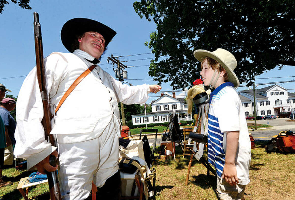 Hour photo / Erik Trautmann Trooper Michael Kean chats with 8 year old Daniel Robson as The Norwalk Historic Society commemorates the 235th anniversary of the Battle of Norwalk Saturday with a Revolutionary War encampment featuring the local re-enactment group, Sheldon's Horse Second Continental Light Dragons, at Mill Hill Historic Park.
