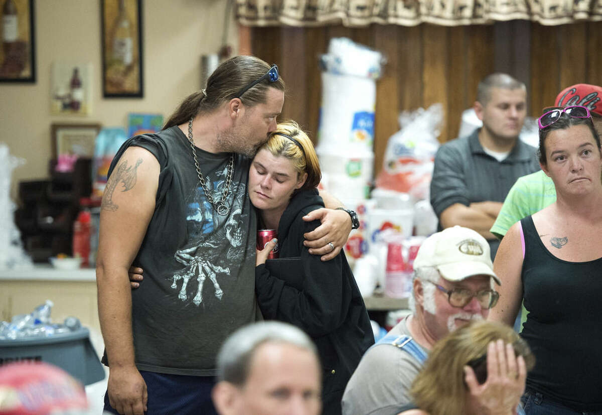 James Logan and his wife Lisa embrace during a community meeting for evacuees as a wildfire burns near Clearlake, Calif., Tuesday, Aug. 4, 2015. Firefighters made some progress Tuesday afternoon with some help from light rain that fell in the area. (AP Photo/Josh Edelson)