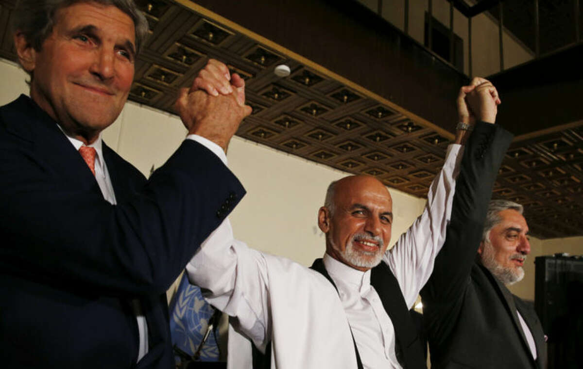 U.S. Secretary of State John Kerry, left, and Afghanistan's presidential candidates Ashraf Ghani, centre, and Abdulah Abdullah hold their arms in the air together after announcing a deal for the auditing of all Afghan election votes at the United Nations Compound in Kabul, Saturday, July 12, 2014. (AP Photo/Jim Bourg, Pool)