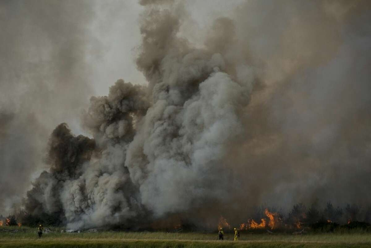 In this Aug. 3, 2015, photo, firefighters work to contain a brush fire near the South Jetty at Fort Stevens State Park in Warrenton, Ore. Numerous other wildfires in California, Washington state and Oregon took off as the effects of drought and summer heat turned the West Coast combustible. (Joshua Bessex/Daily Astorian via AP) MANDATORY CREDIT