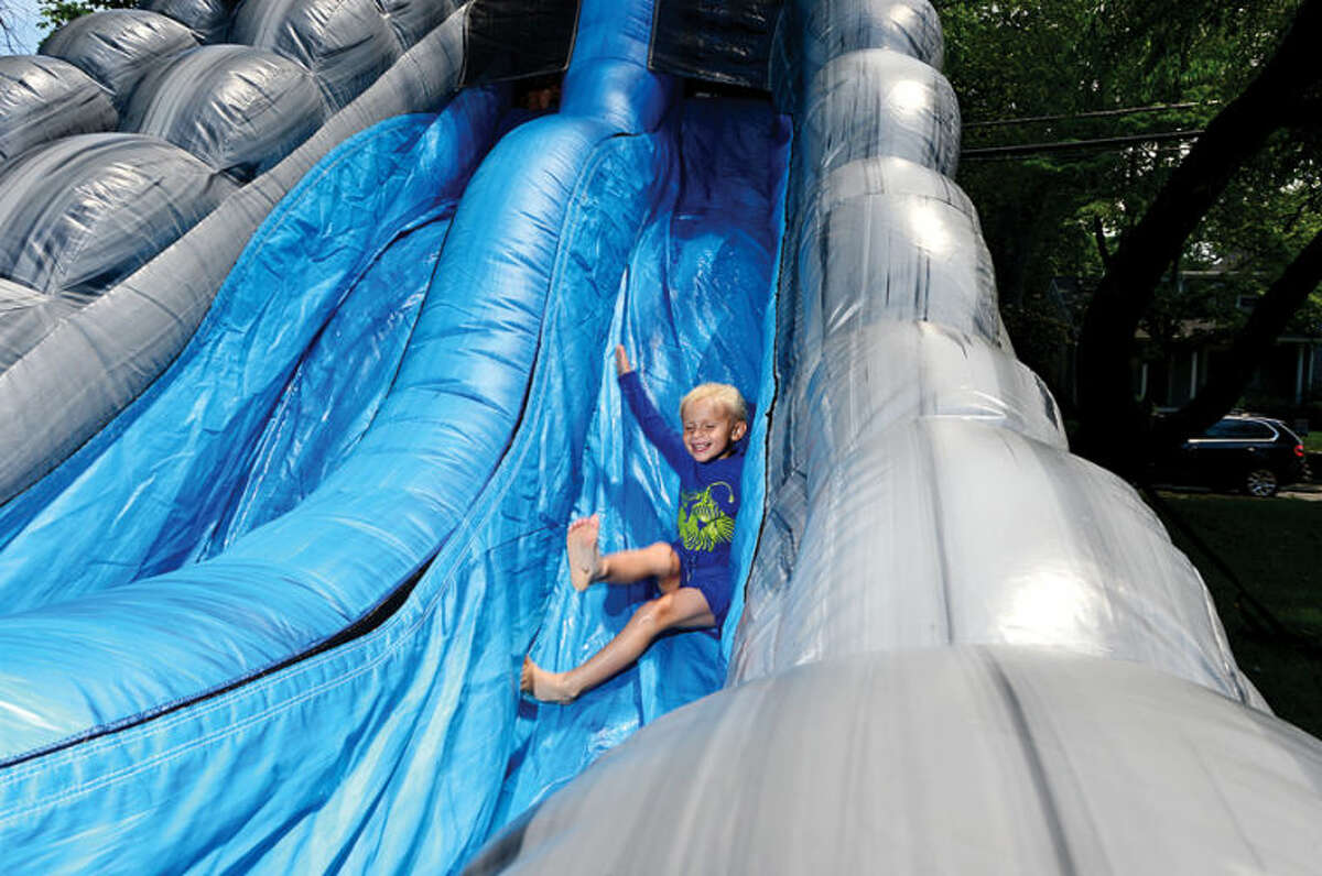 Hour photo / Erik Trautmann 3 year old Bodie Yallop enoys the giant slde at the 44th Annual River Ramble at Pinkney Park Saturday.
