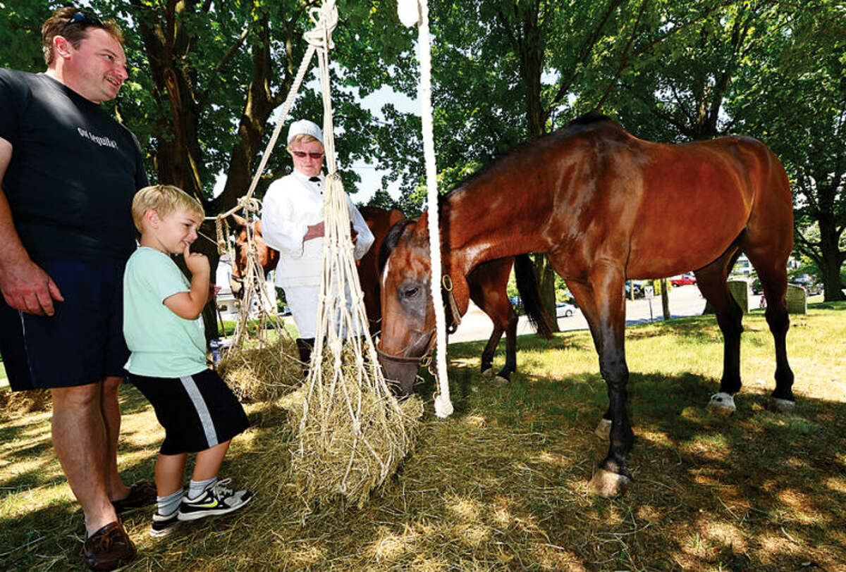 Hour photo / Erik Trautmann Glenn Morrell and his son Tommy, 5, are shown Prince the Horse by Dave Goodrich as The Norwalk Historic Society commemorates the 235th anniversary of the Battle of Norwalk Saturday with a Revolutionary War encampment at the Mill Hill Historic Park featuring the local re-enactment group, Sheldon's Horse Second Continental Light Dragons.