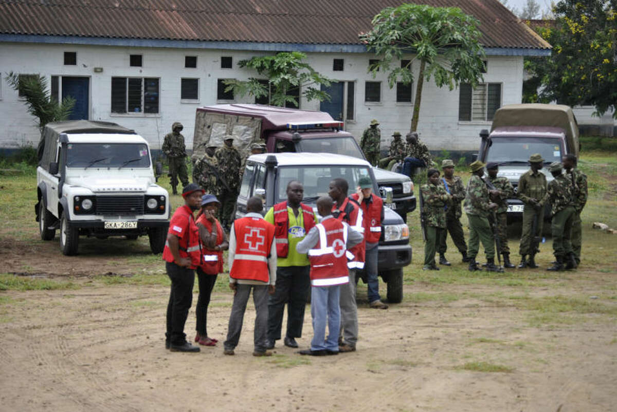 Security personnel and Kenya Red Cross officials stand at the site where gunmen attacked, in Gamba Kenya, Sunday, July 6, 2014. Eighteen people were killed in overnight attacks by the gunmen in two counties on the Kenyan coast, where last month al-Qaida-linked militants claimed responsibility for killing 65 people, the Kenya Red Cross said Sunday. The Sunday attacks took place in the towns of Hindi in Lamu county and Gamba in Tana River, the Kenya Red Cross chief Abbas Gulet said. Al-Qaida-linked al-Shabab militants from Somalia claimed responsibility for the attacks. (AP Photo)