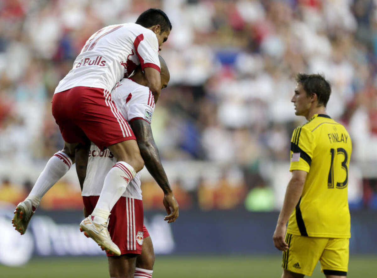 New York Red Bulls' Tim Cahill, top, jumps on teammate Thierry Henry after Henry scored a goal on the Columbus Crew during the first half of an MLS soccer match, Saturday, July 12, 2014, in Harrison, N.J. Crew's Ethan Finlay (13) walks by during the celebration. (AP Photo/Julio Cortez)