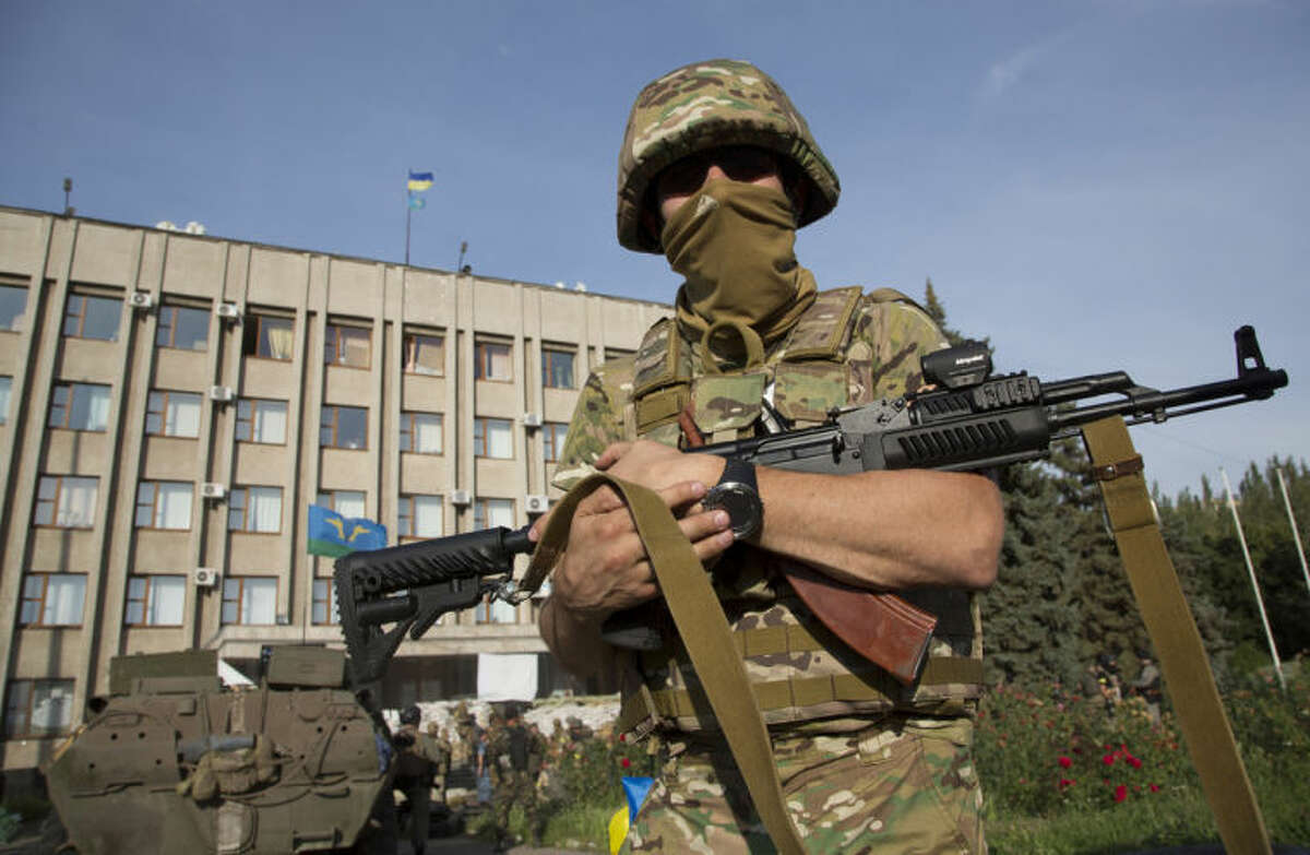 An Ukrainian government army soldier stands in front of the government building with a Ukrainian flag on the roof in the city of Slovyansk, Donetsk Region, eastern Ukraine Saturday, July 5, 2014. By late afternoon on Saturday, Ukrainian troops were fully in control of rebel headquarters in Slovyansk, a city of about 100,000 that has been a center of the fighting between Kiev's troops and the pro-Russian insurgents. (AP Photo/Dmitry Lovetsky)