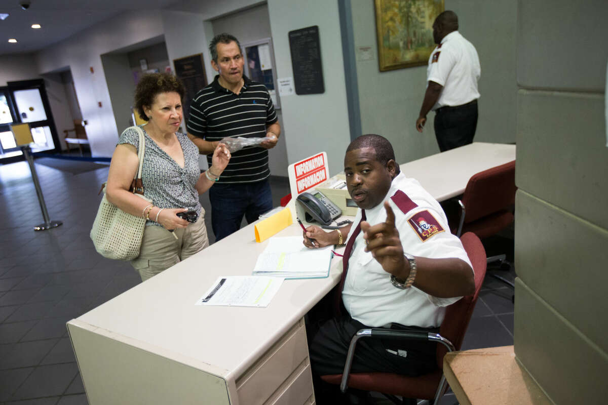 Hour photo/Chris Palermo. Charles Hankerson guides Amparo Ochoa and Henry Jimenez at Norwalk City Hall Wednesday afternoon.