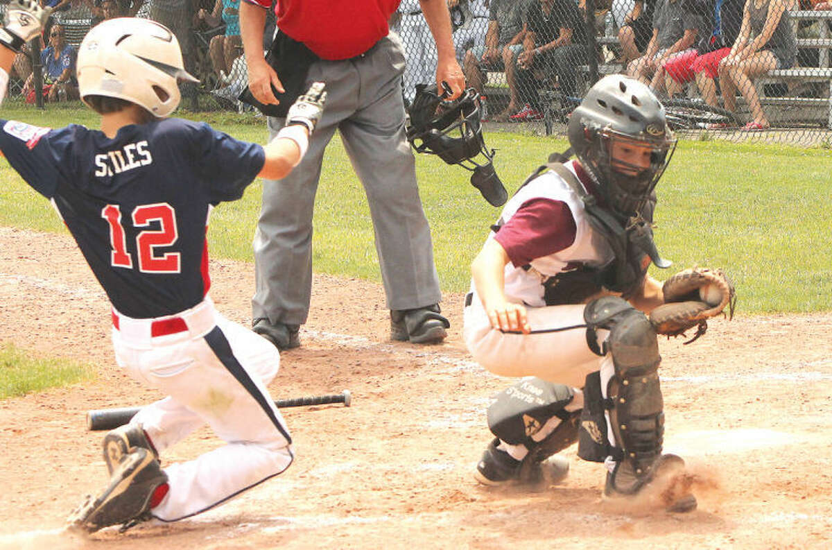 Hour photo/Joe Ryan - Mitchell Stiles of the Norwalk 10-year-old Little League All-Stars slides into home plate safely with the game-winning run in the bottom of the sixth as Stamford National catcher Mike Edwards tries to turn to make the tag during Saturday's District 1 title series game in Stamford. Norwalk won the game, forcing a winner-take-all showdown on Sunday.