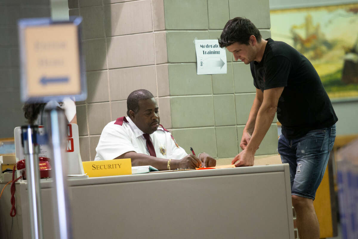 Hour photo/Chris Palermo. Charles Hankerson helps Zoltan Bona at Norwalk City Hall Wednesday afternoon.