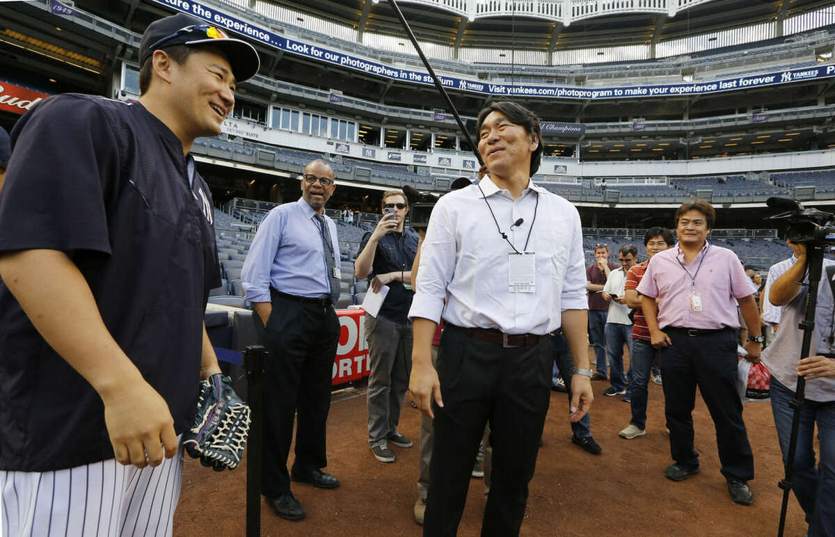 New York Yankees starting pitcher Masahiro Tanaka, left, talks with former Yankee Hideki Matsui before a baseball game between the Boston Red Sox and the Yankees, Wednesday, Aug. 5, 2015, at Yankee Stadium in New York. Matsui was the 2009 World Series Most Valuable Player. (AP Photo/Kathy Willens)