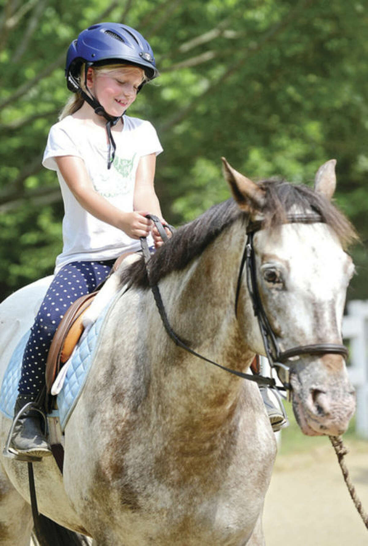 Hour photo / Erik Trautmann Hannah Schonberg gets to ride Quebec during the Wishes for Horses summer camp Wednesday. Wishes for Horses is a non-profit 501 (3) c summer camp set up to help children have a horseback riding experience who might not otherwise have the chance to do so.