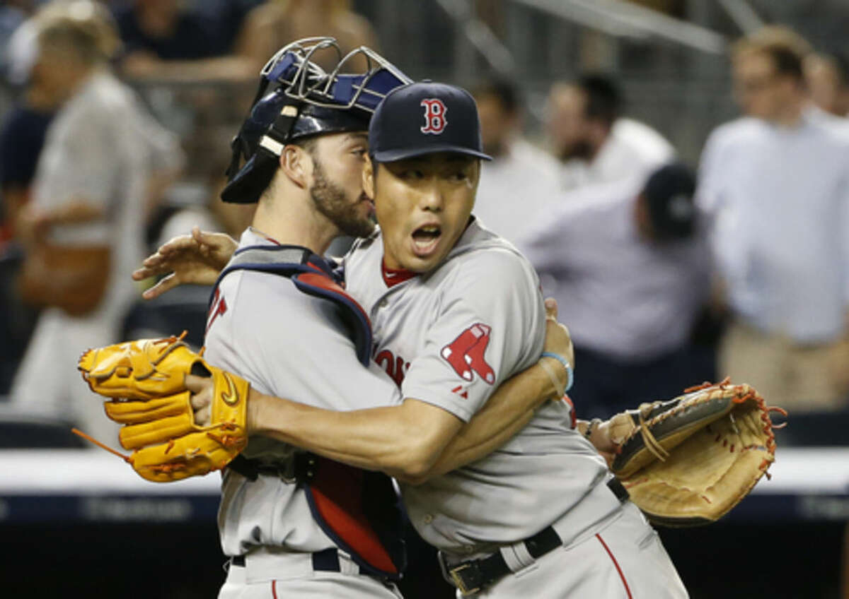 Boston Red Sox catcher Blake Swihart, left, embraces Red Sox relief pitcher Koji Uehara after Uehara earned the save in a 2-1 victory over the New York Yankees in a baseball game at Yankee Stadium in New York, Wednesday, Aug. 5, 2015. (AP Photo/Kathy Willens)