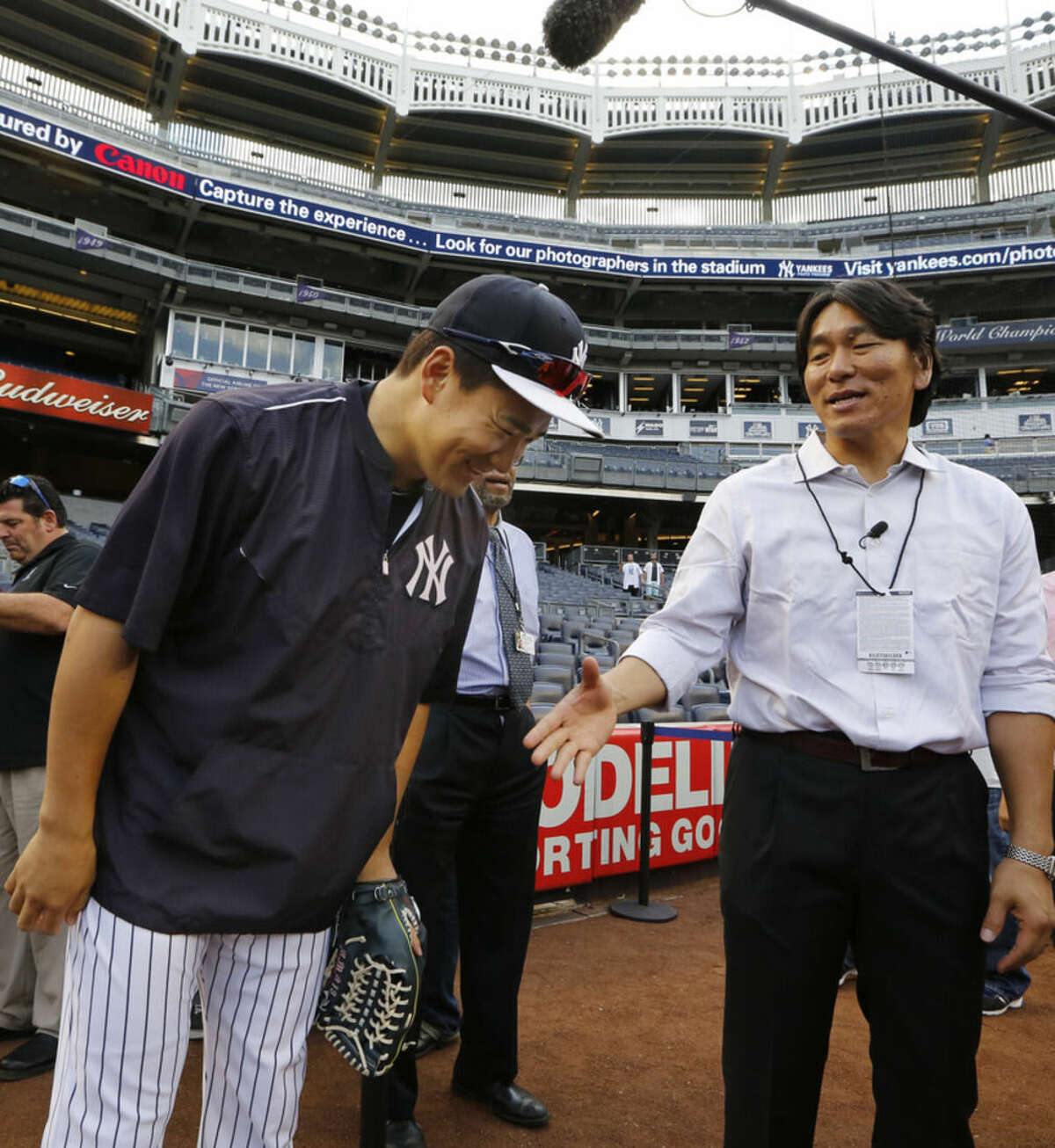 New York Yankees starting pitcher Masahiro Tanaka, left, bows in respect to former Yankee Hideki Matsui before a baseball game between the Boston Red Sox and the Yankees, Wednesday, Aug. 5, 2015, at Yankee Stadium in New York. Matsui was the 2009 World Series Most Valuable Player. (AP Photo/Kathy Willens)