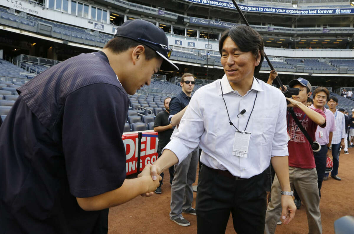 New York Yankees starting pitcher Masahiro Tanaka, left, greets former Yankee Hideki Matsui before a baseball game between the Boston Red Sox and the Yankees, Wednesday, Aug. 5, 2015, at Yankee Stadium in New York. Matsui was the 2009 World Series Most Valuable Player. (AP Photo/Kathy Willens)