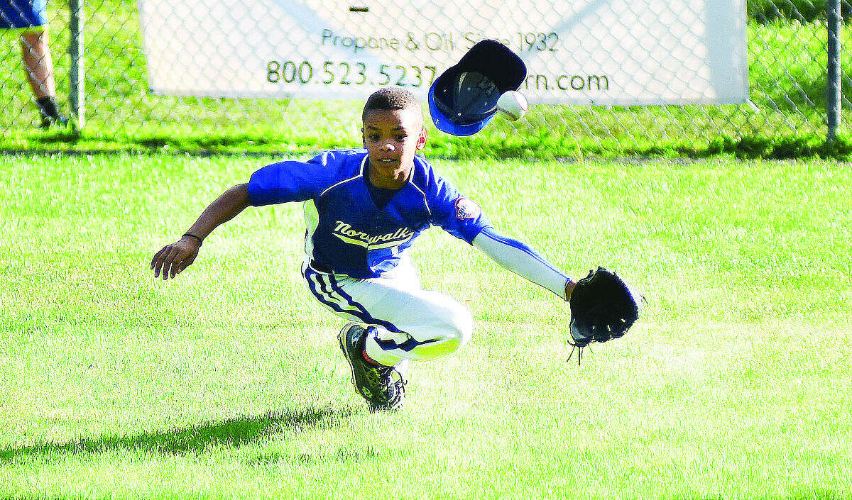 Hour photo/John Nash - Norwalk's AJ Robinson tries to come up with a spectacular diving catch during Wednesday's loser's bracket final between Norwalk and Swanzey, N.H., at the New England Regional 11-year-old Cal Ripken Tournament in Dover, N.H. Norwalk won, 4-3, to advance to the regional championship game.