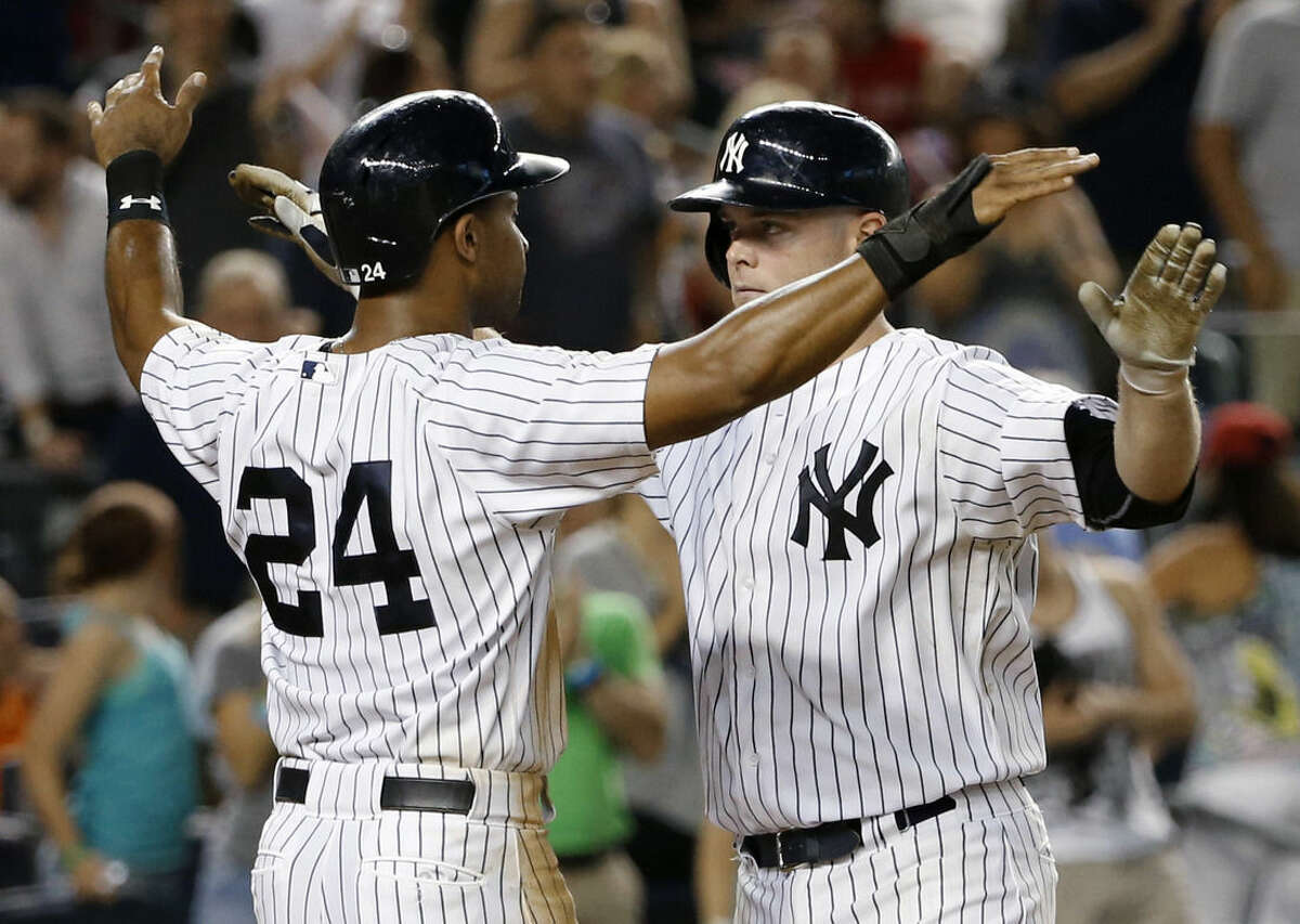 New York Yankees' Chris Young (24) and Brian McCann celebrate at the plate after Young scored on McCann's seventh-inning home run off Boston Red Sox relief pitcher Craig Breslow in a baseball game at Yankee Stadium in New York, Tuesday, Aug. 4, 2015. (AP Photo/Kathy Willens)