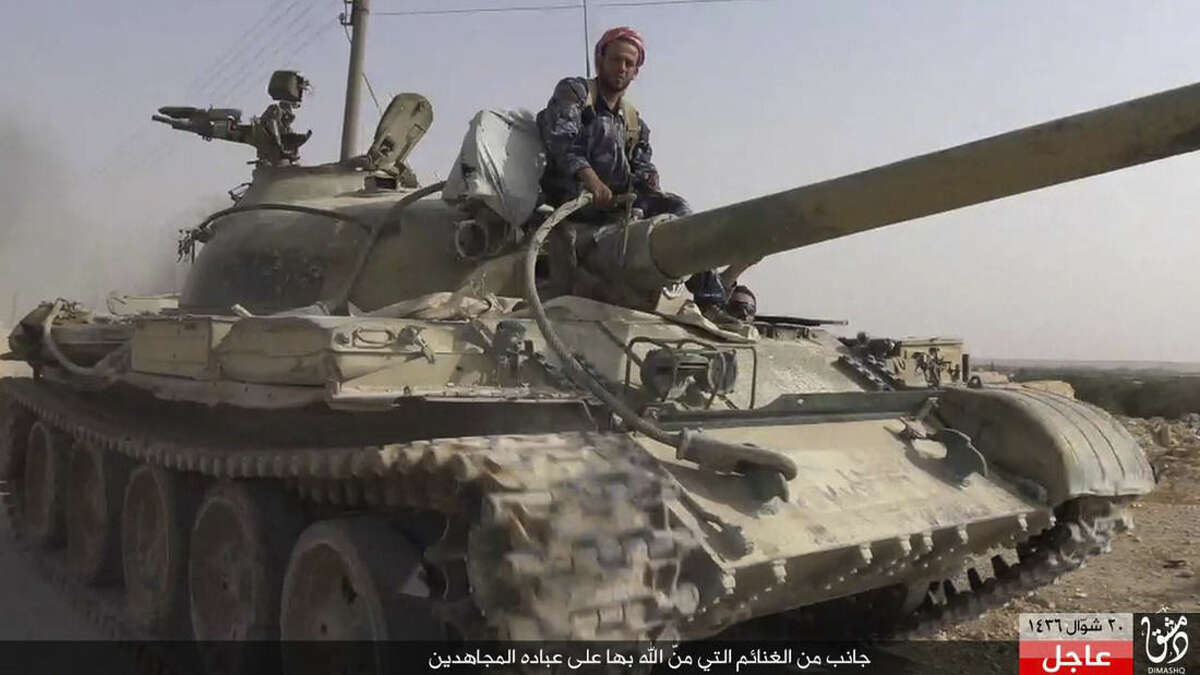 In this picture released Wednesday, Aug. 5, 2015 by the Rased News Network a Facebook page affiliated with Islamic State militants, an Islamic State militant sits on a tank they captured from Syrian government forces, in the town of Qaryatain southwest of Palmyra, central Syria. The Islamic State group on Thursday seized a key town in central Syria following heavy clashes with President Bashar Assad's forces, in the militants' biggest advance since capturing the historic town of Palmyra in May, Syrian activists said. (Rased News Network a Facebook page affiliated with Islamic State militants via AP)