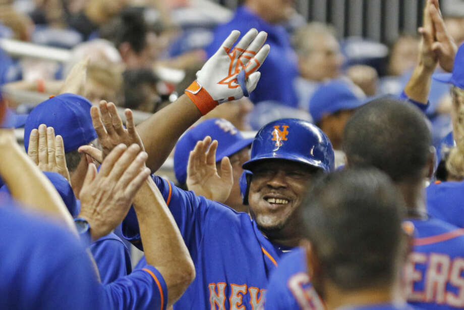 New York Mets' Juan Uribe, center, celebrates his fifth-inning, three-run home run against the Miami Marlins with teammates during a baseball game in Miami, Wednesday Aug. 5, 2015. (AP Photo/Joe Skipper)
