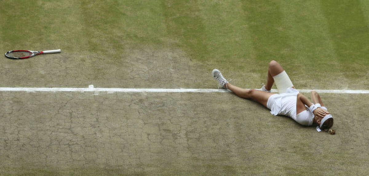 Petra Kvitova of Czech Republic celebrates defeating Eugenie Bouchard of Canada in their women's singles final at the All England Lawn Tennis Championships in Wimbledon, London, Saturday, July 5, 2014. (AP Photo/Gareth Fuller, Pool)