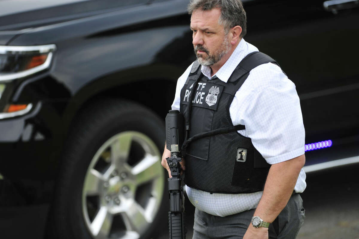 A police officer walks on the scene of a reported shooting in Nashville, Tenn., Wednesday, Aug. 5, 2015. A suspect wielding a hatchet and a gun inside a Nashville-area movie theater died after exchanging gunshots with a police team that stormed the theater, police said Wednesday. (John Partipilo/The Tennessean via AP)