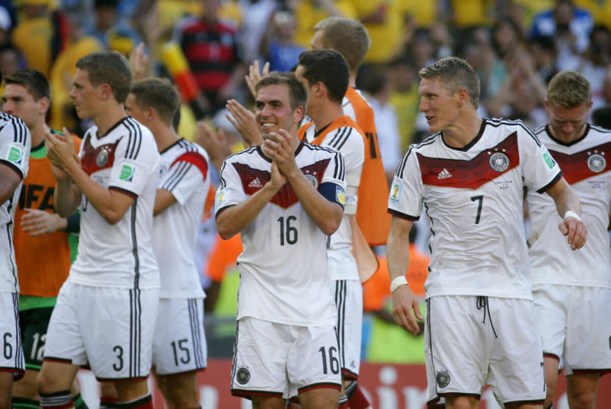 Germany's Philipp Lahm, center, smiles at the end of the World Cup quarterfinal soccer match between Germany and France at the Maracana Stadium in Rio de Janeiro, Brazil, Friday, July 4, 2014. Germany won the match 1-0. . (AP Photo/David Vincent)