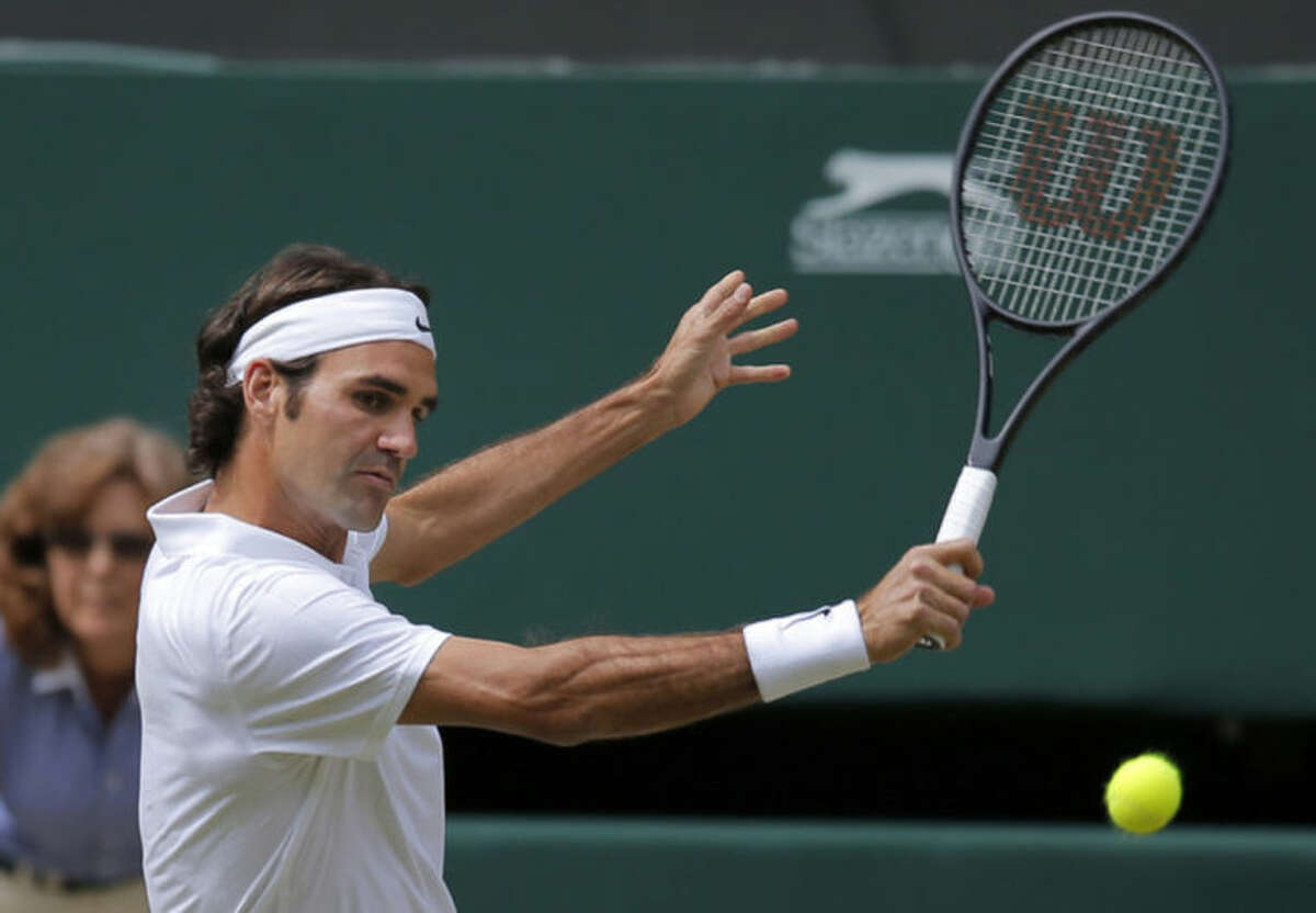 Roger Federer of Switzerland plays a return to Novak Djokovic of Serbia during their men's singles final at the All England Lawn Tennis Championships in Wimbledon, London, Sunday July 6, 2014. (AP Photo/Pavel Golovkin)