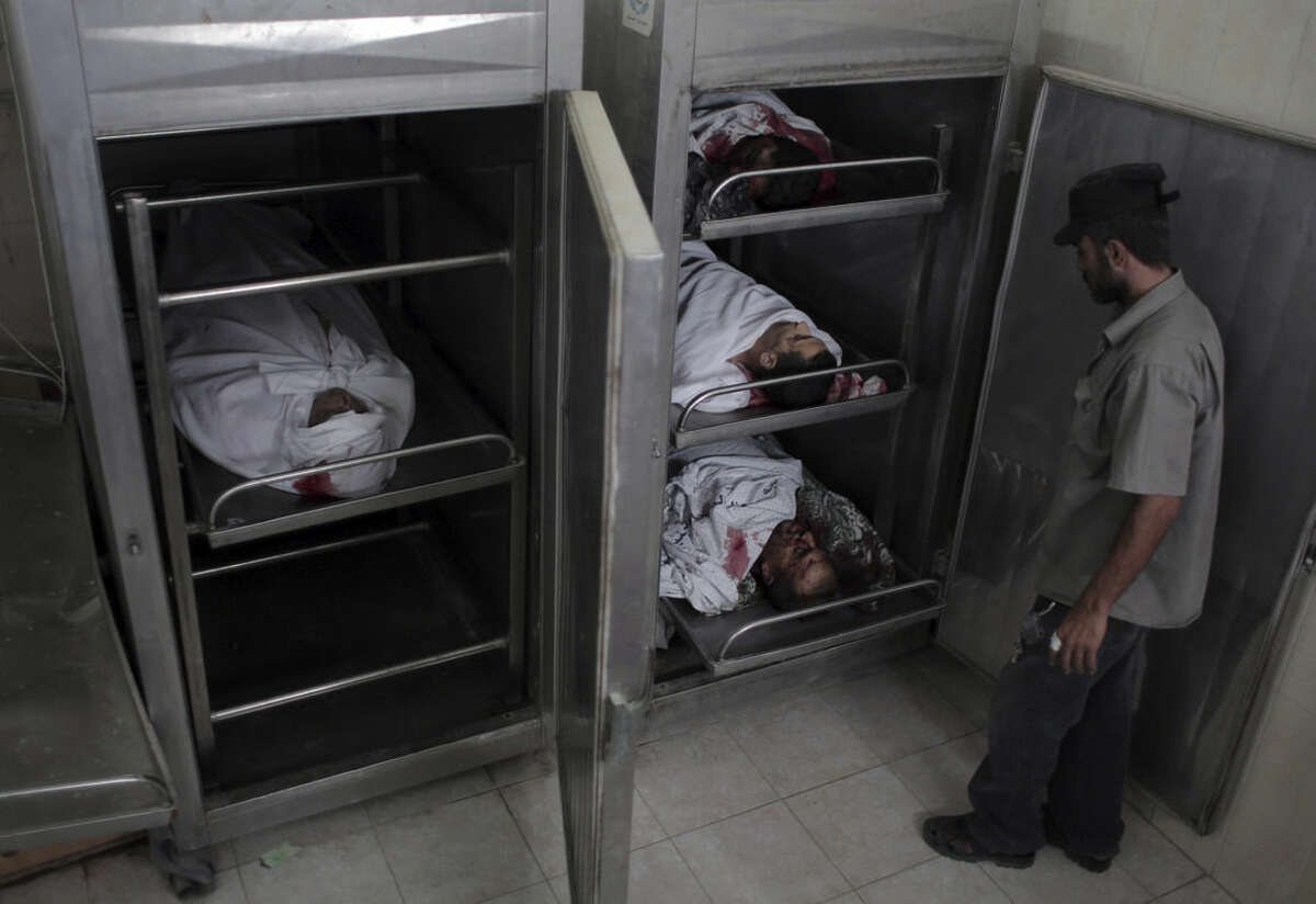 A Palestinian man stands next to the bodies of four men who were killed by an explosion, in the morgue of the Najjar hospital in Rafah, southern Gaza Strip, Thursday, Aug. 6, 2015. Palestinian health official said at least four Palestinians from the same family were killed and 13 people were injured in the Gaza Strip on Thursday by an explosion of Israeli military ordnance left over from last summer's war. (AP Photo/ Khalil Hamra)