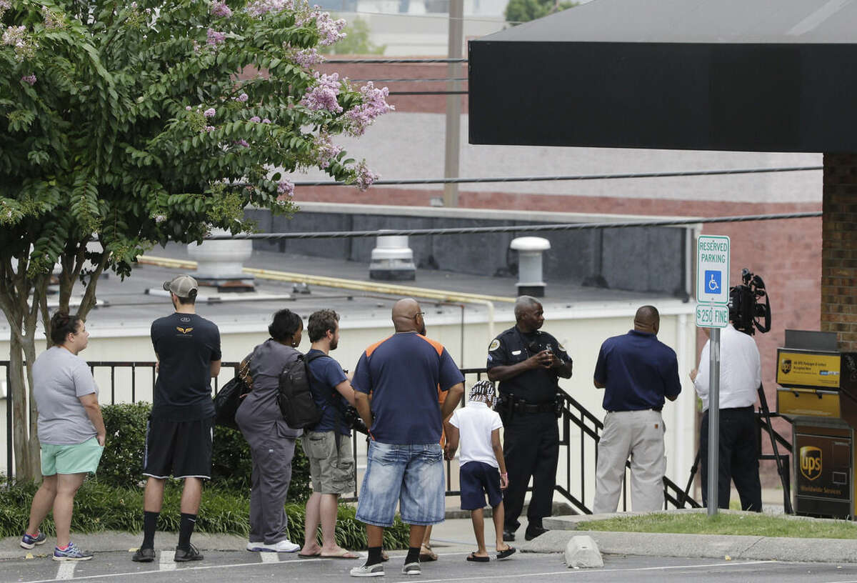 People look down at the back of a movie theater complex following a shooting Wednesday, Aug. 5, 2015, in Antioch, Tenn. A man armed with a hatchet and gun unleashed a volley of pepper spray at audience members inside a movie theater, exchanging fire with a responding officer before being shot dead by police as he tried to escape out the back of the theater only to encounter a SWAT team, police said. (AP Photo/Mark Humphrey)