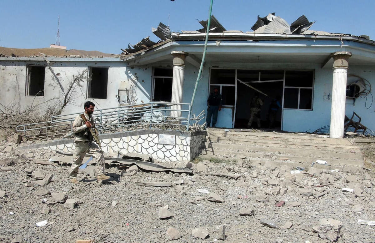 An Afghan security guard inspects the site of a truck bombing attack in Logar province, east of Kabul, Afghanistan, Thursday, Aug. 6, 2015. An Afghan official says a suicide bomber exploded a truck loaded with explosives outside provincial government offices in the country's east, killing many people and wounding a dozen. (AP Photo/Ihsanullah Mahjoor)