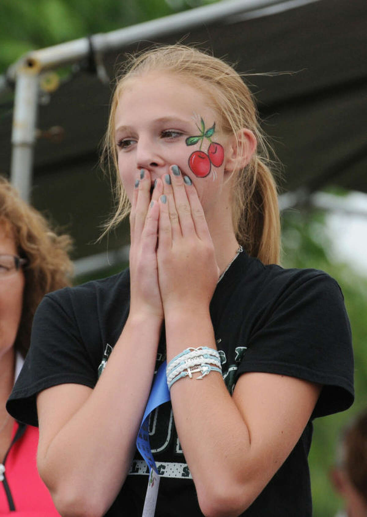 Chloe Bartz, 13, from Niles, Mich., reacts after winning the women's division during the 41st International Cherry Pit-Spitting Championship on Saturday, July 5, 2014, at Tree-Mendus Fruit Farm in Eau Claire, Mich. (AP Photo/The Herald-Palladium, Don Campbell)