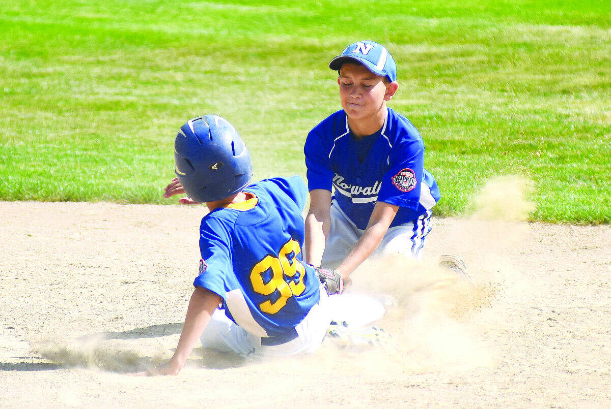 Hour photo/John Nash - Norwalk shortstop Ben Boccanfuso, top, lays down a tag on Newtown's Matt Pietroyazio during Thursday's Cal Ripken All-Stars 11-year-old New England Regional Tournament championship game at Beckwith Park's Keyes Field in Dover, N.H. Newtown won the title with a 6-5 win over Norwalk.