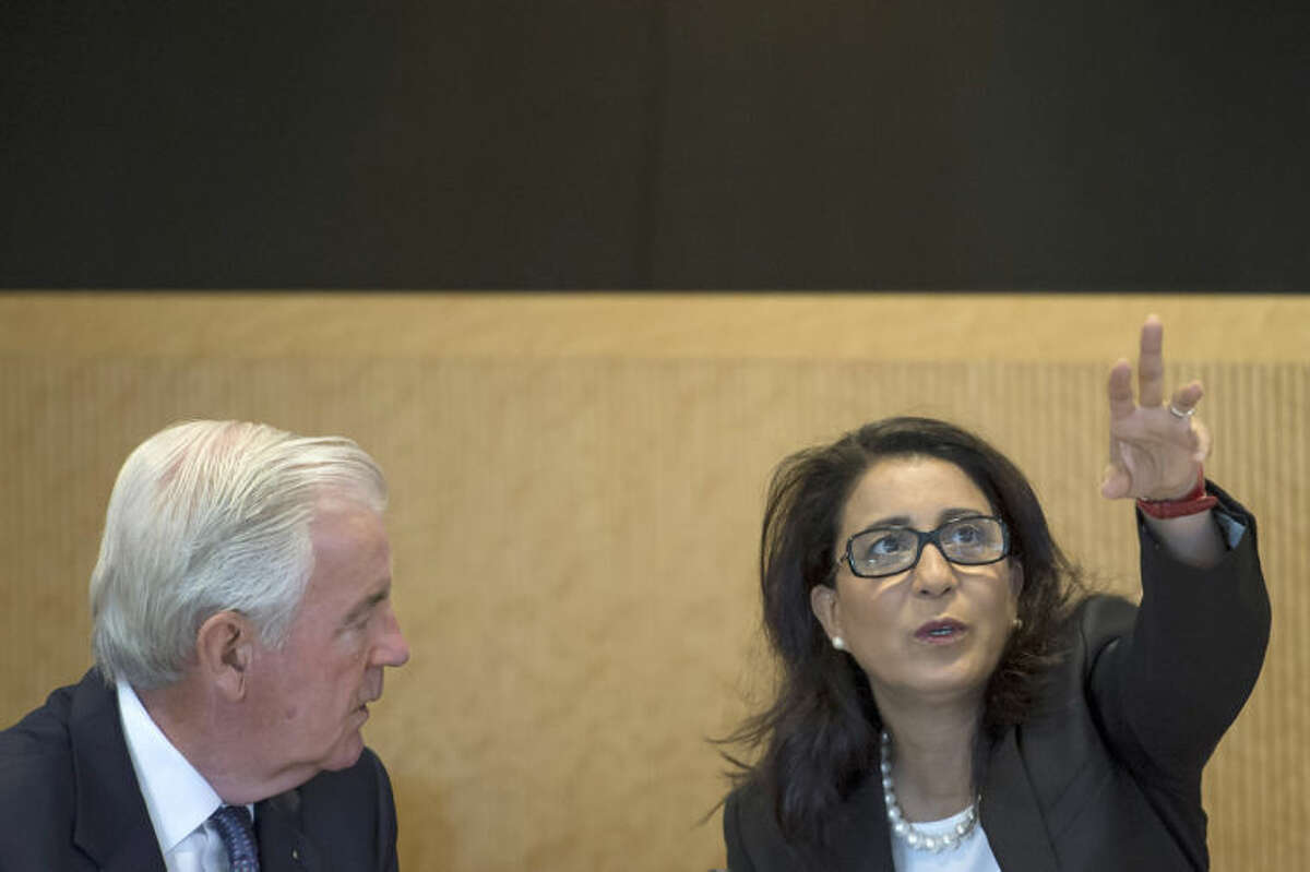 Members of the International Olympic Committee, IOC, Craig Reedie from Britain, left, and Nawal El Moutawakel of Morocco, right, talk to each other prior to the opening of the executive board meeting at the IOC headquarters in Lausanne, Switzerland, on Monday, July 7, 2014. (AP Photo/Keystone,Jean-Christophe Bott)