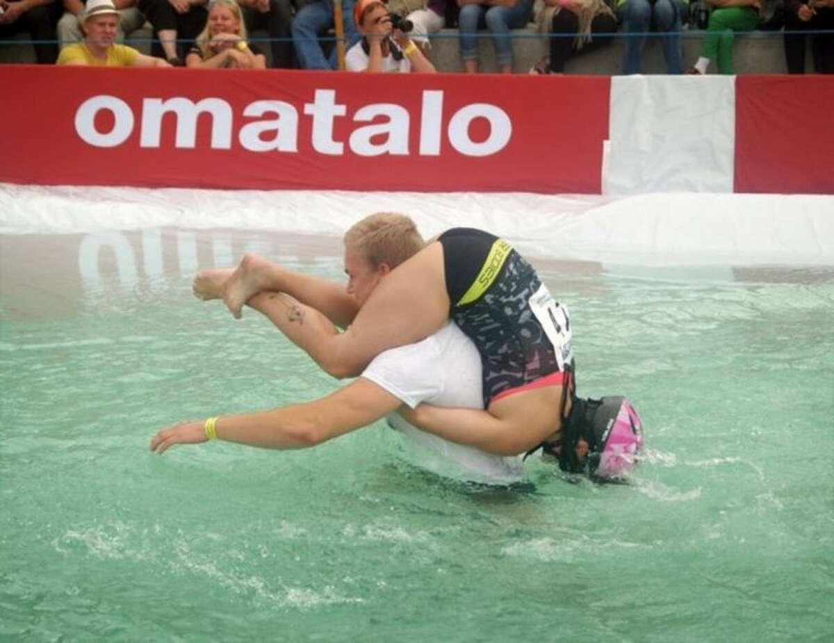 Ville Parviainen and Janette Oksman from Vantaa, Finland go on to win the Wife Carrying World Championships, held in Sonkajarvi, Finland, Saturday, 5 July, 2014. (AP Photo/Pekka Moliis, Lehtikuva) FINLAND OUT