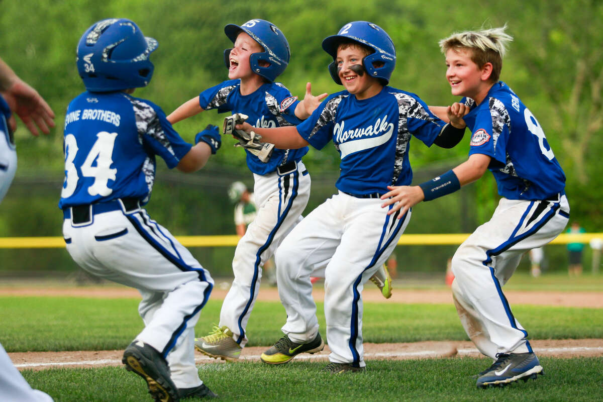 Hour photo/Chris Palermo. Norwalk players celebrate after their 11-1 win over Dover, N.H. in the 2015 New England 9U Regional Championship at Burnt Hill Park in Hebron, Conn. Thursday night.