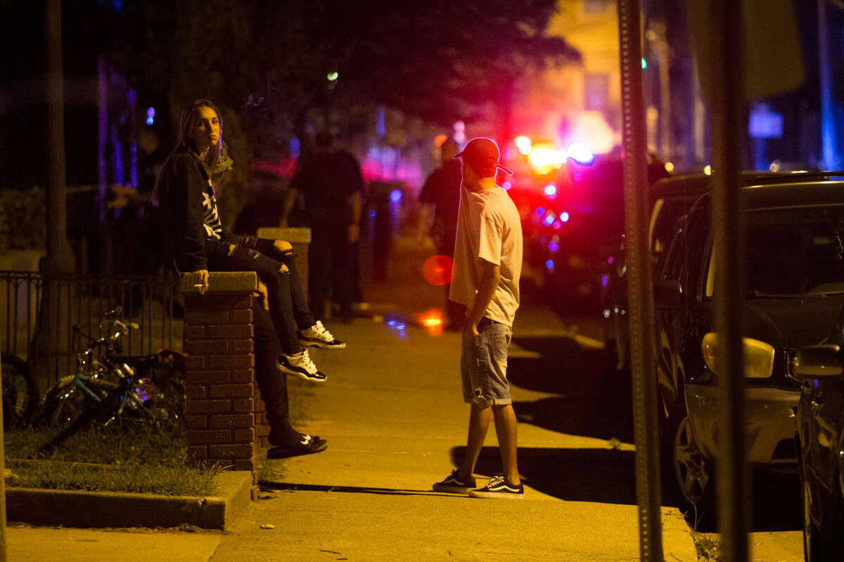Hour photo/Chris Palermo Bystanders watch as Norwalk Police investigate a reported shooting at the Washington Village Housing Complex on Water Street Thursday night.