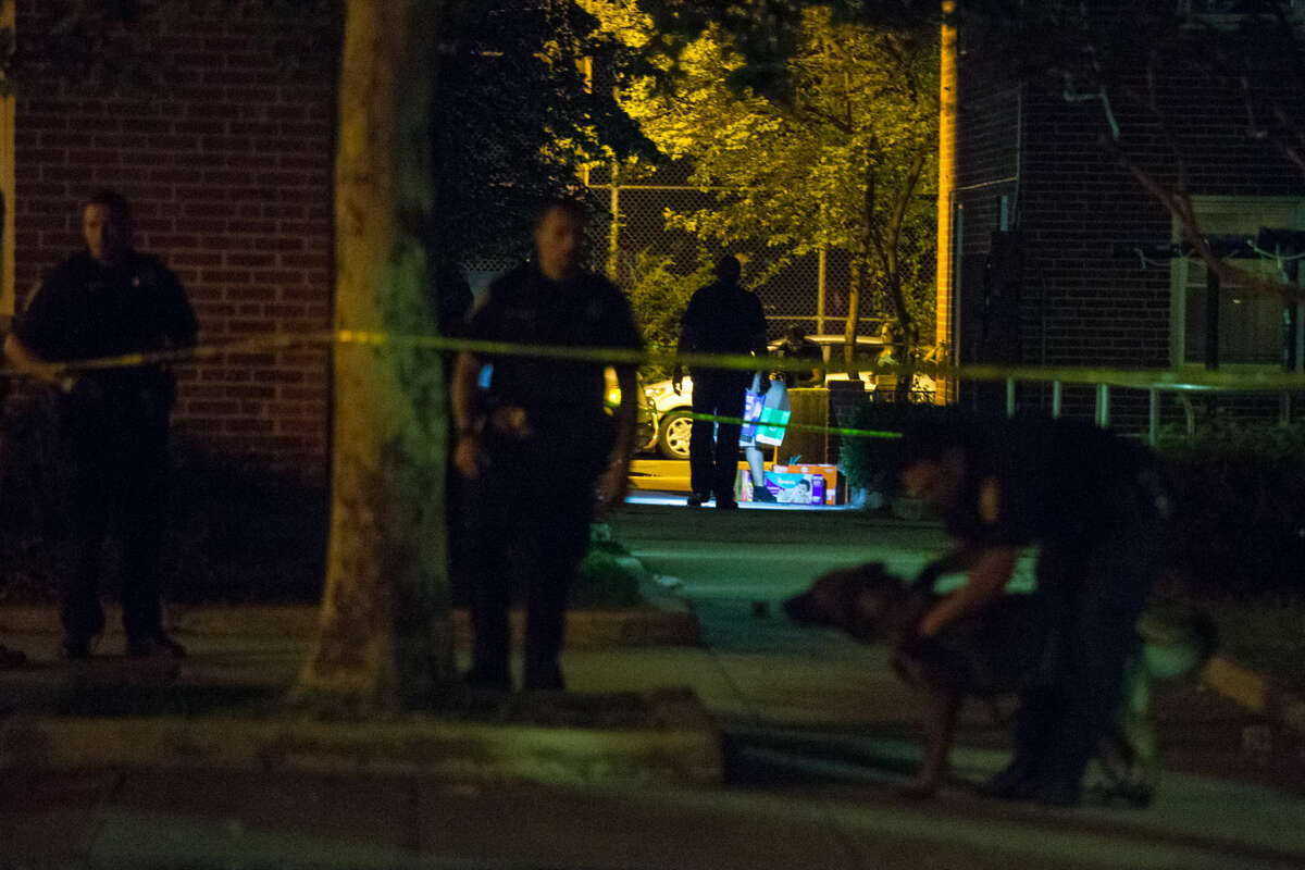 Hour photo/Chris Palermo Norwalk Police investigate a reported shooting at the Washington Village Housing Complex on Water Street Thursday night.