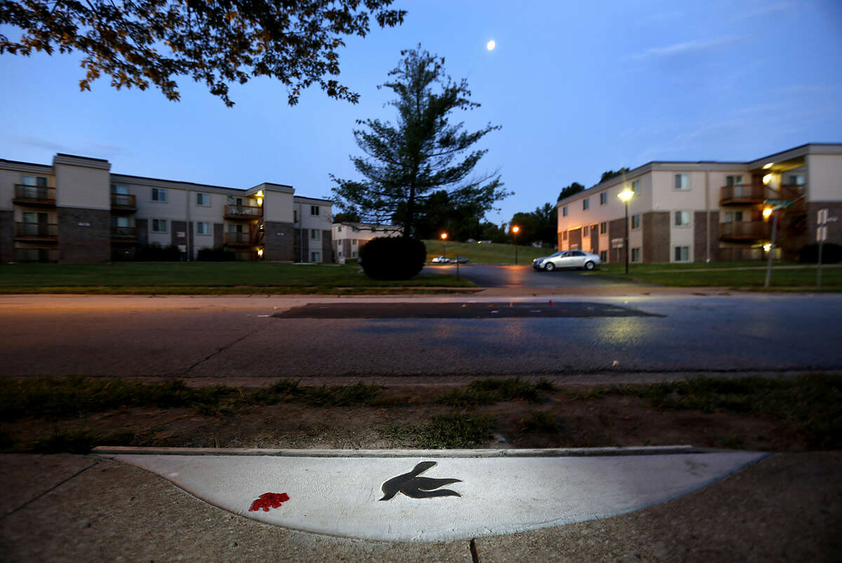 In this Sunday, Aug. 2, 2015, photo, a marker in the shape of a dove is embedded in the sidewalk near the spot where Michael Brown was shot and killed by police officer Darren Wilson in Ferguson, Mo. A year ago, Ferguson was thrust into the national spotlight after the death of Brown giving way to the