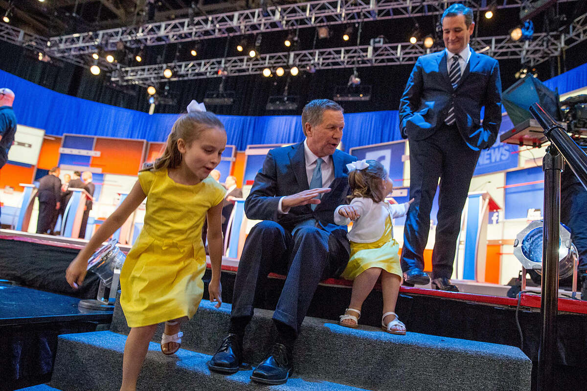 Republican presidential candidate Ohio Gov. John Kasich, center, says hello to the daughters of Sen. Ted Cruz, R-Texas, right, Catherine, 4, second from right, and Caroline, 7, left, during a commercial break as they participate in the first Republican presidential debate at the Quicken Loans Arena, Thursday, Aug. 6, 2015, in Cleveland. (AP Photo/Andrew Harnik)