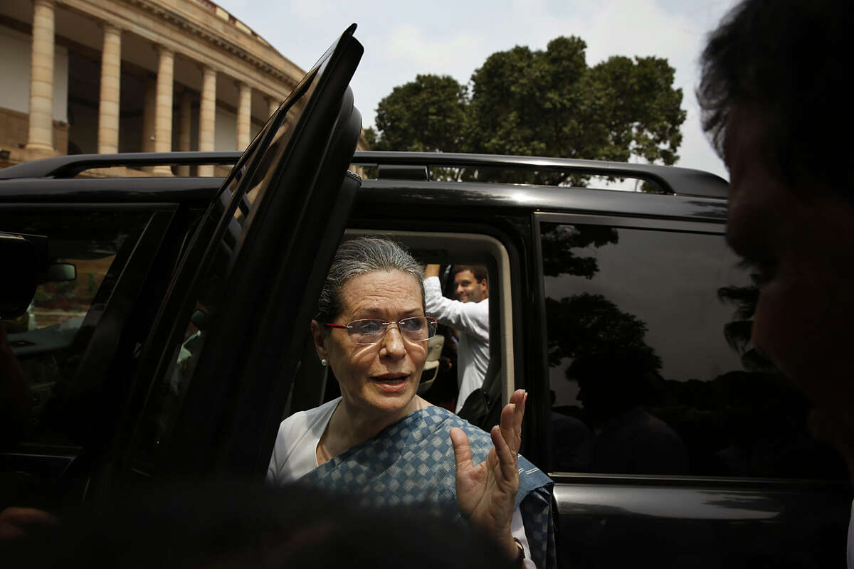 India's opposition Congress party president Sonia Gandhi, front accompanied by her son and party vice-president Rahul Gandhi, behind, prepares to leave in their vehicle after a protest in the Parliament premises in New Delhi, India, Thursday, Aug. 6, 2015. The opposition continued their protests Thursday demanding that two leaders of the ruling Bharatiya Janata Party resign for allegedly helping a former Indian cricket official facing investigation for financial irregularities. (AP Photo/Manish Swarup)