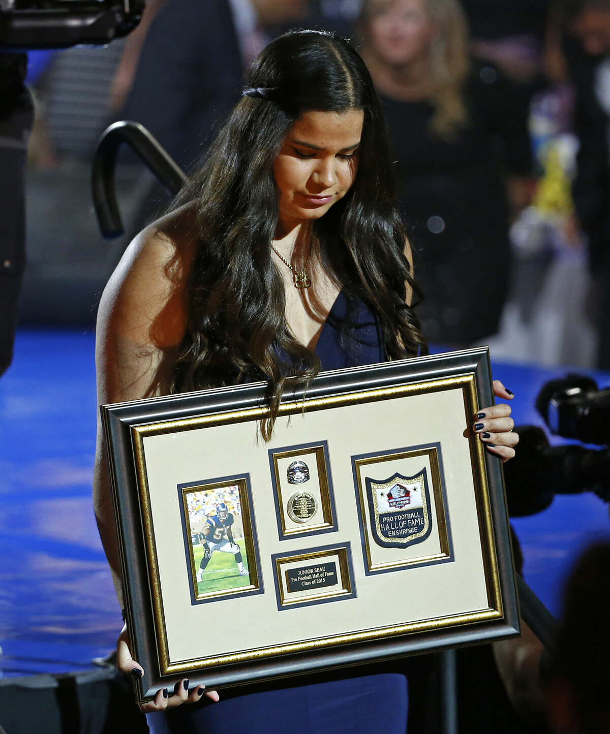 Daughter of Pro Football Hall of Fame inductee Junior Seau, Sydney Seau, accepts a framed remembrance in place of her father's gold jacket during the Gold Jacket Ceremony in Canton, Ohio, Thursday, Aug. 6, 2015. (AP Photo/Gene J. Puskar)