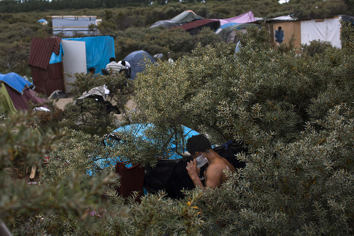 A migrant washes himself at a camp set near Calais, northern France, Thursday, Aug. 6, 2015. Thousands of migrants have been scaling fences near the Channel Tunnel linking the two countries and boarding freight trains or trucks destined for Britain. (AP Photo/Emilio Morenatti)