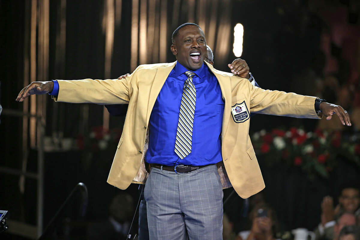 Pro Football Hall of Fame inductee Tim Brown slips on his gold jacket with the help of his presenter, his brother Donald Kelly, rear, during the gold jacket ceremony in Canton, Ohio, Thursday, Aug. 6, 2015. (AP Photo/Gene J. Puskar)