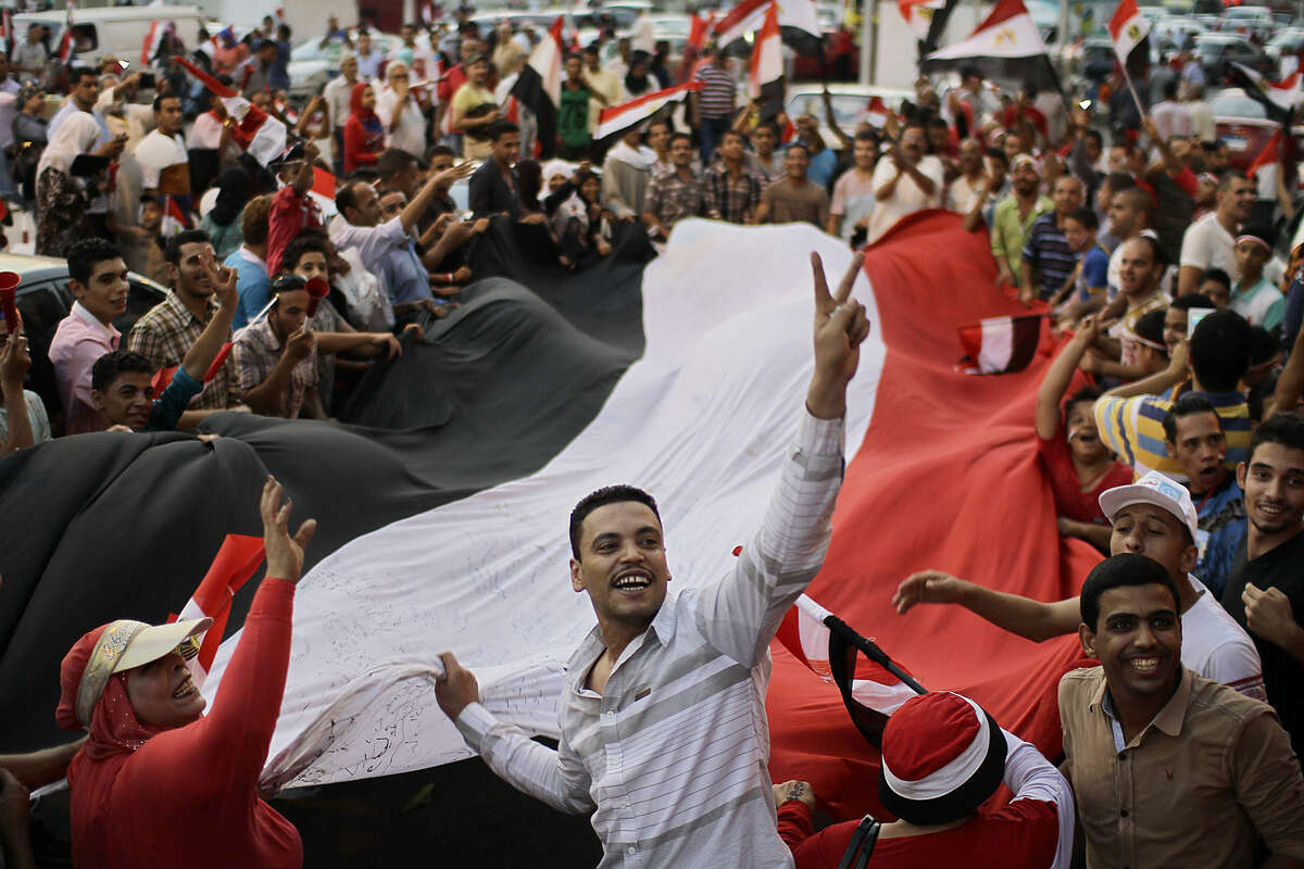 People celebrate the new Suez Canal opening while gathering around Tahrir Square in downtown Cairo, Egypt, Thursday, Aug. 6, 2015. With much pomp and fanfare, Egypt on Thursday unveiled a major extension of the Suez Canal billed by its patron, President Abdel-Fattah el-Sissi as a historic achievement needed to boost the country's ailing economy after years of unrest. (Ahmed Abd El-Latif/El Shorouk newspaper via AP)