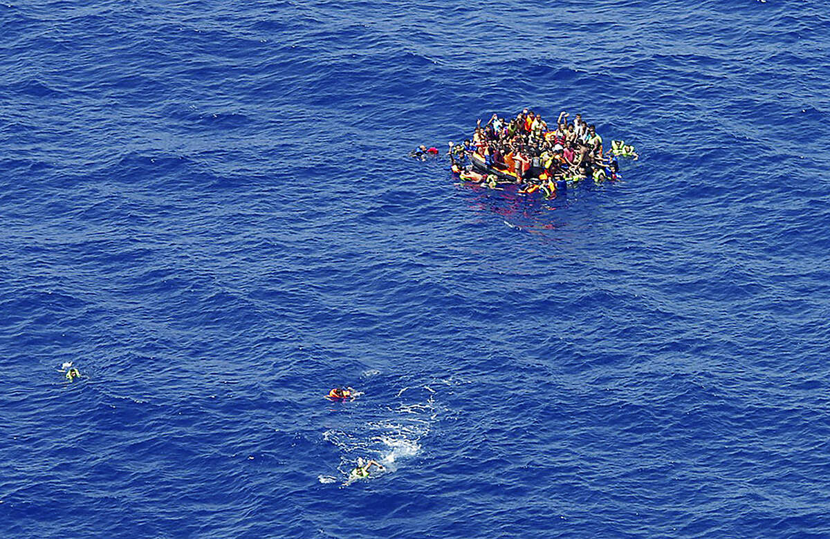 In this photo taken on Wednesday, Aug. 5, 2015 and made available Thursday, Aug. 6, migrants swim while others climbed onto a rescue dinghy wait for rescuers on the scene of the capsizing and sinking of a fishing boat in the Mediterranean sea off Libya. The Italian coast guard and Irish navy said at least 367 people were saved, although 25 bodies also were found as many other are feared to have died during the capsizing of the fishing boat in the latest human smuggling tragedy. (Italian Navy VIA AP Photo)